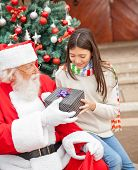 Girl taking Christmas gift from Santa Claus outside house