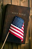 holy bible with american flag on wooden background