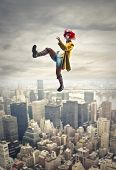 pretty clown walking on a tightrope above the city
