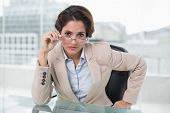 Dubious businesswoman looking at camera in bright office
