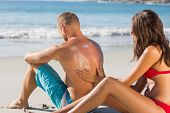 Smiling woman on the beach putting sun cream on her boyfriends back