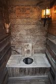 stock photo of outhouses  - Old time wooden outhouse with electric lamp South Dakota - JPG