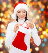 christmas, x-mas, winter, happiness concept - smiling woman in santa helper hat with small gift box