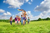 stock photo of kites  - Cute happy active kids boys and girls run with kite in the park and having fun - JPG