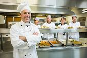 image of maturity  - Proud mature head chef posing in a modern kitchen with his colleagues in the background - JPG