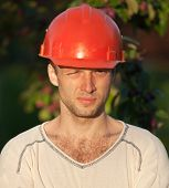 Closeup Portrait Of Young Construction Worker With Squinting Eyes