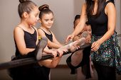 stock photo of ballet barre  - Beautiful little ballet dancers listening to her teacher - JPG