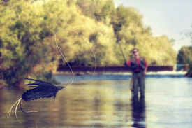 stock photo of fly rod  - a person fly fishing in a river with a fly in the foreground - JPG