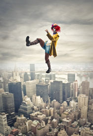 pic of laughable  - pretty clown walking on a tightrope above the city - JPG