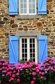 Fragment of a typical country house with blue shutters in Brittany, France
