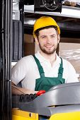 stock photo of forklift driver  - Happy male forklift driver in yellow safety helmet - JPG