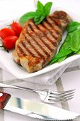 Grilled New York steak served on a plate with vegetables