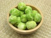 Wooden Bowl With Brussels Sprouts On Rattan Underlay