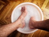 stock photo of douching  - Man soaking his feet in a washbowl - JPG
