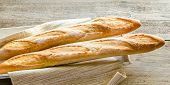 foto of baguette  - Two baguettes laying close on the wooden tray