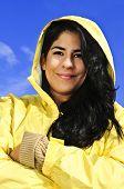 Portrait of beautiful smiling brunette girl wearing yellow raincoat against blue sky