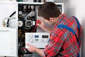 pic of gas-pipes  - Technician servicing the gas boiler for hot water and heating - JPG