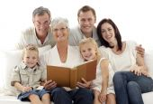 stock photo of girl reading book  - Grandmother reading a book to her children and parents in living - JPG