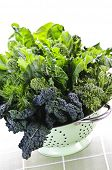Dark green leafy fresh vegetables in metal colander