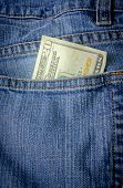 stock photo of twenty dollars  - A twenty dollar bill sticking out the back pocket of denim blue jeans - JPG
