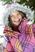 Portrait of happy teenage girl in winter ski coat with fur hood