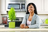 Smiling black woman in modern kitchen interior