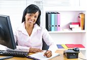 Smiling young black business woman writing at desk in office