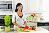 Smiling black woman cutting vegetables in modern kitchen interior