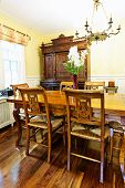 Dining room interior with antique wooden table and chairs in house