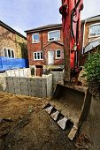 stock photo of backhoe  - Backhoe scoop at residential home renovation construction site - JPG