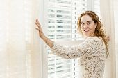 stock photo of lace-curtain  - Happy woman opening curtains on big sunny window with shutters - JPG