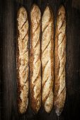 Four whole baguette bread loaves on dark wooden background