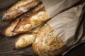 Fresh baked rustic bread loaves in paper bags on dark wood background