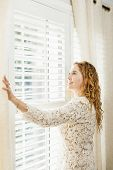 stock photo of lace-curtain  - Happy woman looking out big bright window with curtains and blinds - JPG