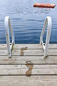 stock photo of wet feet  - Wet footprints on dock with ladder and diving platform at calm summer lake in Ontario Canada - JPG