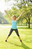 Female fitness instructor doing jumping jacks exercising in green park