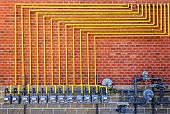 picture of gas-pipes  - Row of natural gas meters with yellow pipes on building brick wall - JPG