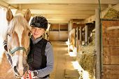 stock photo of stable horse  - Young female rider with horse inside stable - JPG