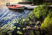 Rowboat tied to dock on beautiful lake at rocky shore with aquatic plants. Ontario, Canada.