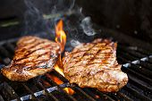 stock photo of charcoal  - Beef steaks cooking in open flame on barbecue grill - JPG