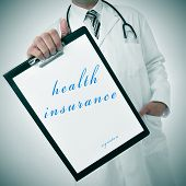a doctor showing a clipboard with the text health insurance written in it