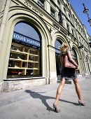SAINT PETERSBURG, RUSSIA - JUNE 15: An upscale shopper walk by a Louis Vuitton store in Saint Peters