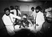 CHARIKAR, AFGHANISTAN - OCT 23: Doctors prepare to amputate the bomb shattered leg of a Northern All