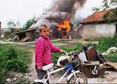 VUCITRN, KOSOVO - JUNE 26: A young ethnic Serb boy watches his house burn to the ground in Vucitrn,