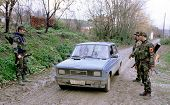 RETMILJE, KOSOVO,  12 NOVEMBER 1998 --- Soldiers of the Kosovo Liberation Army (KLA) stop a car at a makeshift roadblock in the Drenica Triangle.