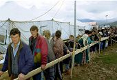 KUKES, ALBANIA, 17 APRIL 1999 -- Kosovar Albanians line up for food between rows of tents at an Ital