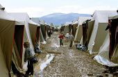 KUKES, ALBANIA, 19 APRIL 1999 -- A river of mud flows between rows of tents housing refugees at an I