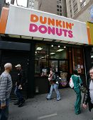 NEW YORK CITY - APRIL 19: Pedestrians walk past a Dunkin' Donuts franchise in New York City, on Frid