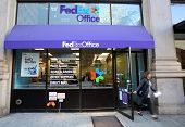 NEW YORK CITY - OCT 20 2013: Pedestrians walk past a FedEx Store retail shop in Manhattan on Sunday,