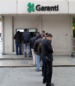 ISTANBUL, TURKEY - SATURDAY, MARCH 8, 2014: Customers wait on line to access money from an ATM machi